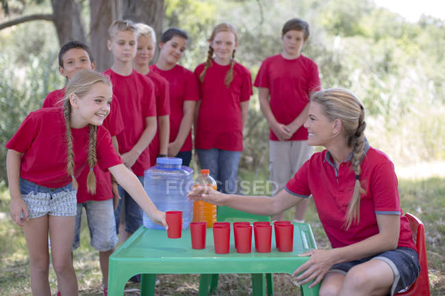 Kids getting refreshment drinks from woman — Stock Photo