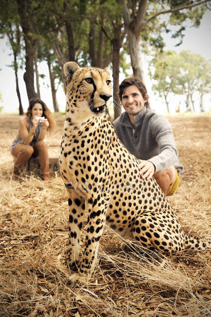 África do Sul, homem de estimação manso chita no prado com mulher no fundo — Fotografia de Stock