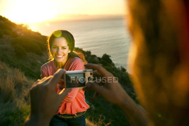 Hombre fotografiando a su novia al atardecer - foto de stock