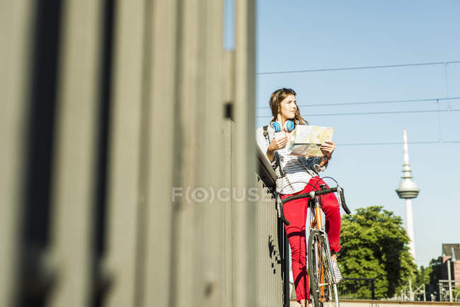 Молодая женщина с велосипедов, держа карты — стоковое фото