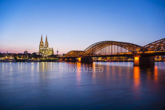 Alemania, Renania del Norte-Westfalia, Colonia, Colonia encendida cathredral y Hohenzollern Bridge de noche - foto de stock