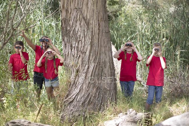 Filhos e mulher em viagem de campo, explorar a natureza com binóculos — Fotografia de Stock