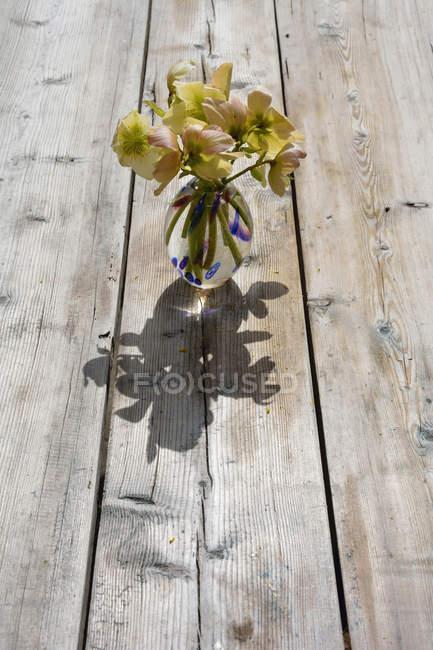 Blumenvase mit Rosenstrauss Winter, Helleborus Niger, auf Holz — Stockfoto
