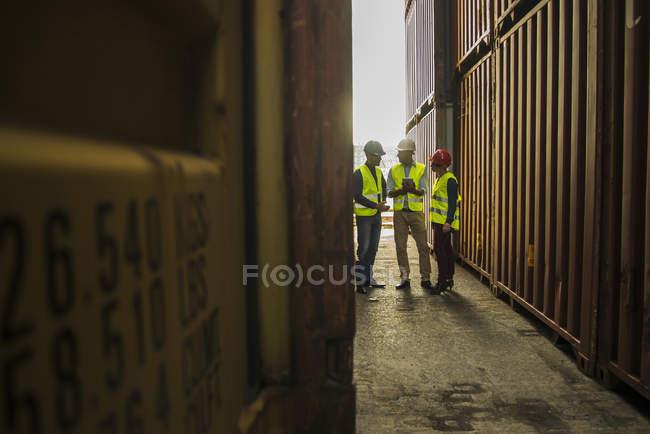 Жінка та двоє чоловіків з безпеки касок говорити в порту контейнерів — стокове фото
