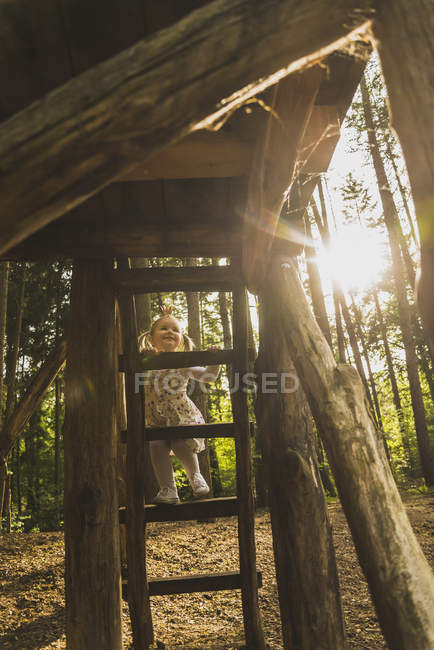 Girl climbing on ladder in forest — Stock Photo