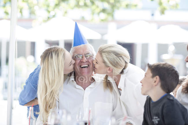 Family celebrating grandfathers birthday in restaurant — Stock Photo