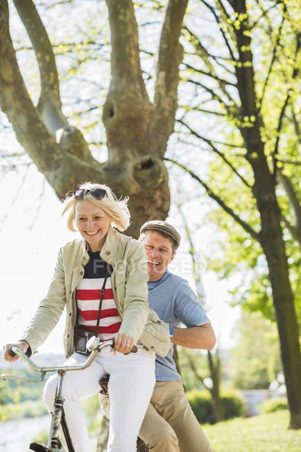 Casal maduro andar de bicicleta no parque, homem sentado no rack — Fotografia de Stock