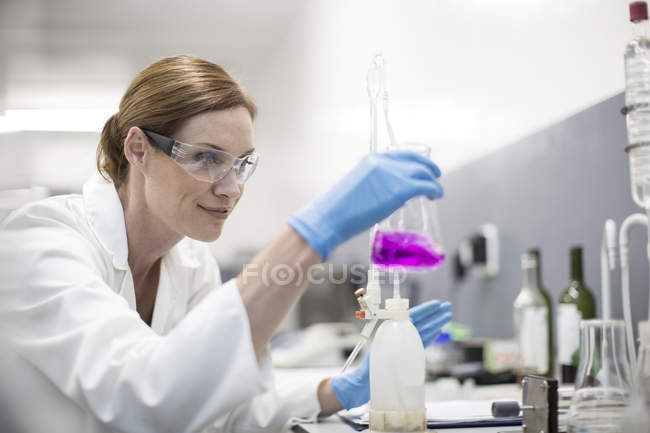 Scientist in lab holding Erlenmeyer flask — Stock Photo
