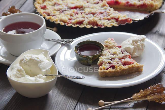 Клубничный пирог из ревеня со взбитыми сливками и чашкой фруктового чая с кусочком на тарелке — стоковое фото
