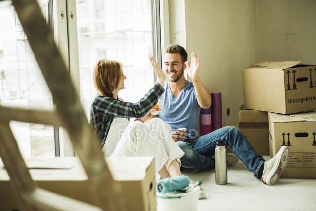 Happy couple having a coffee break from renovating — Stock Photo