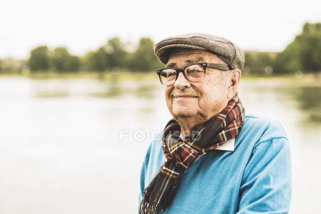 Portrait of smiling senior man wearing glasses and cap — Stock Photo