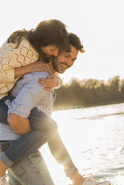 Glückliche junge Paare, die Spaß am Flussufer — Stockfoto