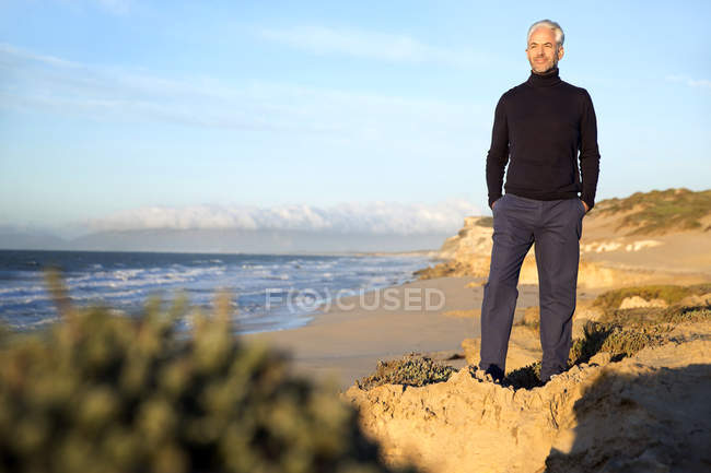 South Africa, man wearing turtleneck standing on rocks at the beach before sunrise — Stock Photo
