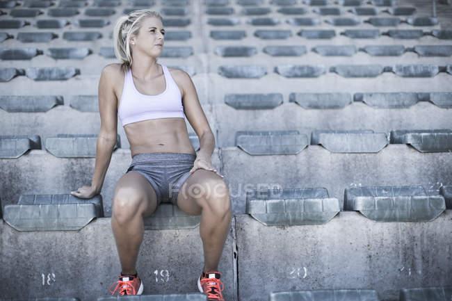 Portrait of sportswoman sitting on grandstand of a stadium — Stock Photo