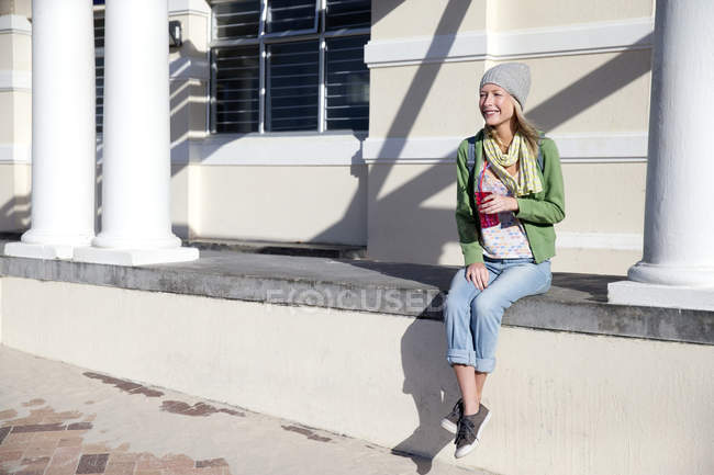 Young woman outdoors holding soft drink — Stock Photo