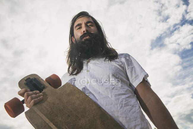 Низкоугольный вид человека хипстерского типа с длинным бортом — стоковое фото