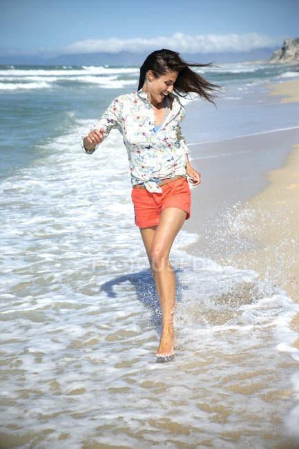 South Africa, happy woman running along the beach at seafront — Stock Photo