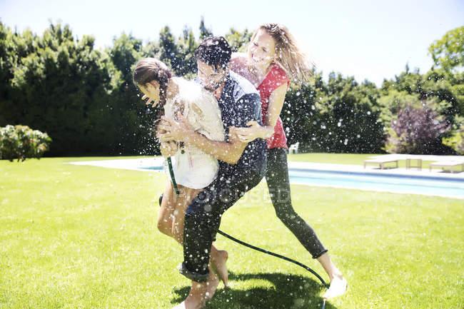 Feliz familia salpicando agua - foto de stock