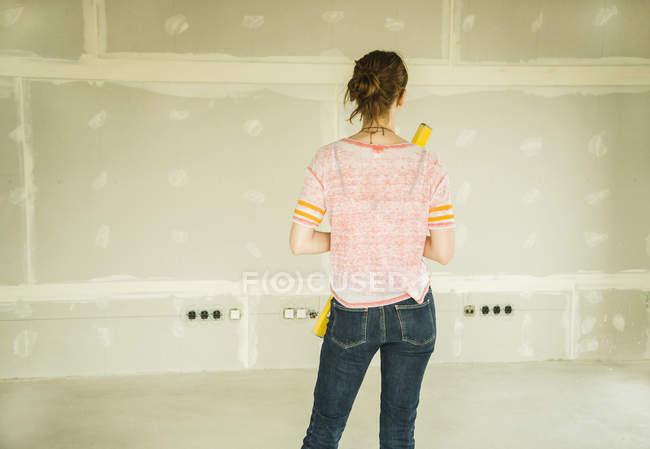 Mujer joven renovando de pie en la pared en blanco - foto de stock