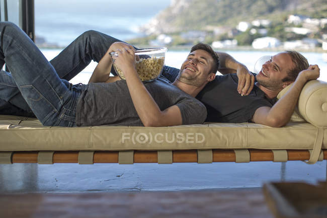 Gay couple relaxing on lounge together — Stock Photo
