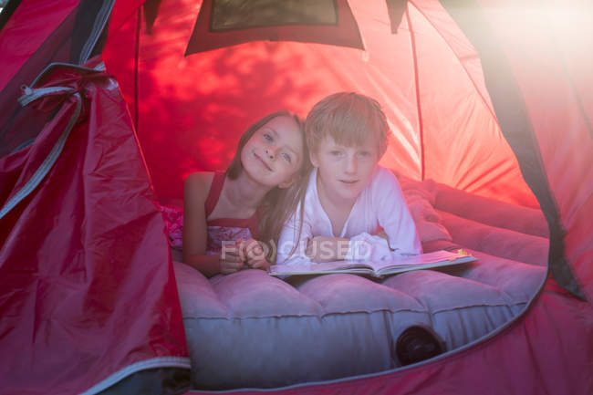 Portrait of brother and sister lying in a red tent with a book — Stock Photo