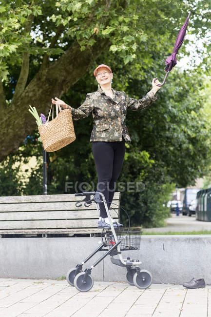 Happy senior woman with wheeled walker — Stock Photo