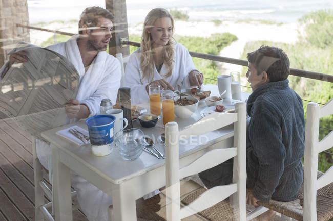 Familie auf der Terrasse des Strandhauses beim Frühstück — Stockfoto