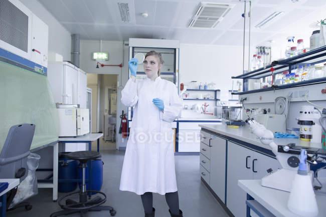 Jeune naturaliste avec boîte de Pétri dans un laboratoire — Photo de stock