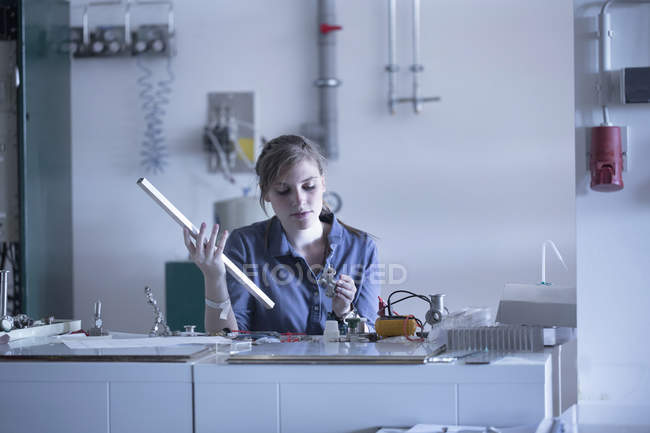 Technician in workshop holding working material — Stock Photo