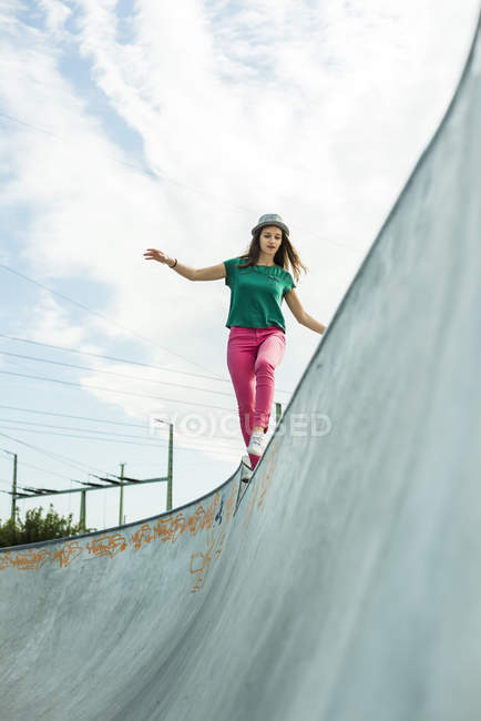Young woman balancing on a wall in a skatepark — Stock Photo