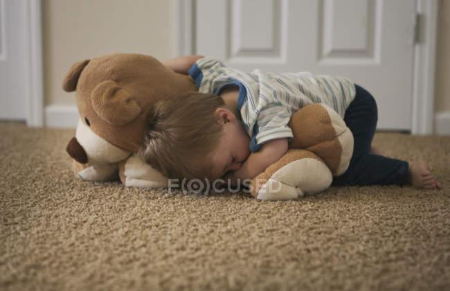 Stanco bambino che dorme sul pavimento con orso — Foto stock