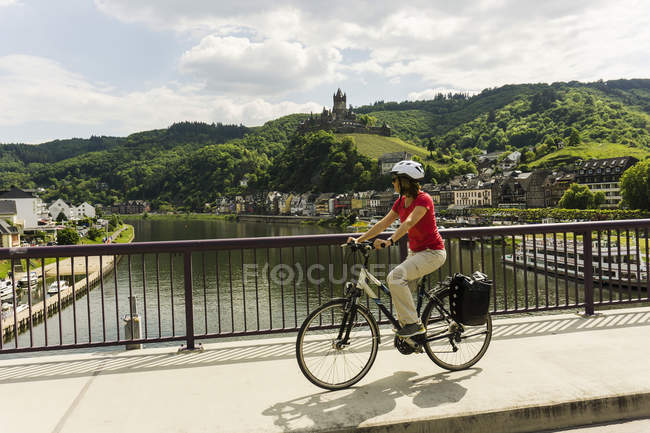 Germany, Cochem, cyclist passing bridge over Moselle — Stock Photo