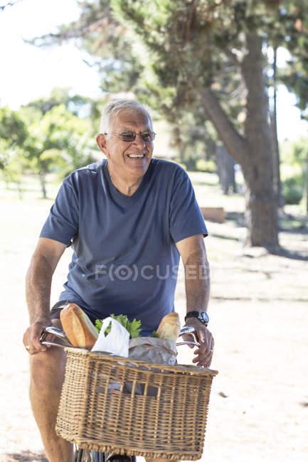 Homme âgé souriant à vélo — Photo de stock