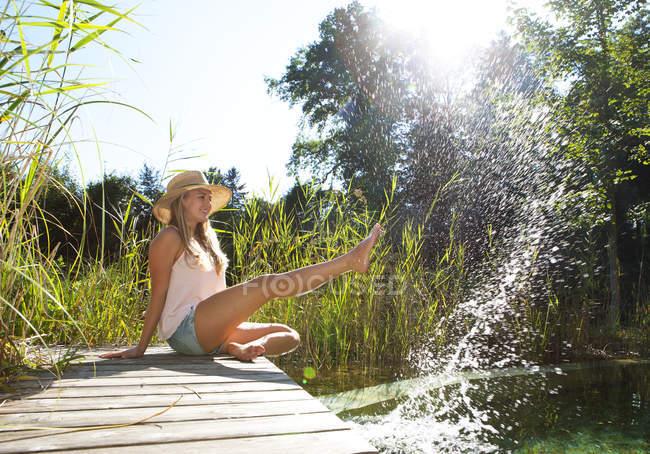 Giovane donna seduta sul lungomare di legno spruzzando con acqua di uno stagno — Foto stock