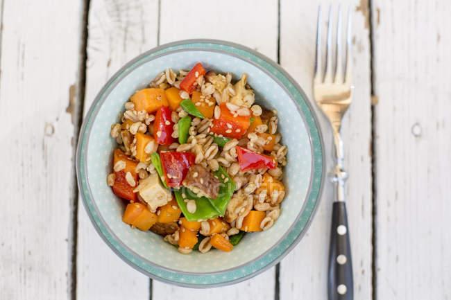 Salade végétalienne au blé d'épeautre, sésame, tofu, poivron rouge, pois mange-tout et carottes dans un bol — Photo de stock