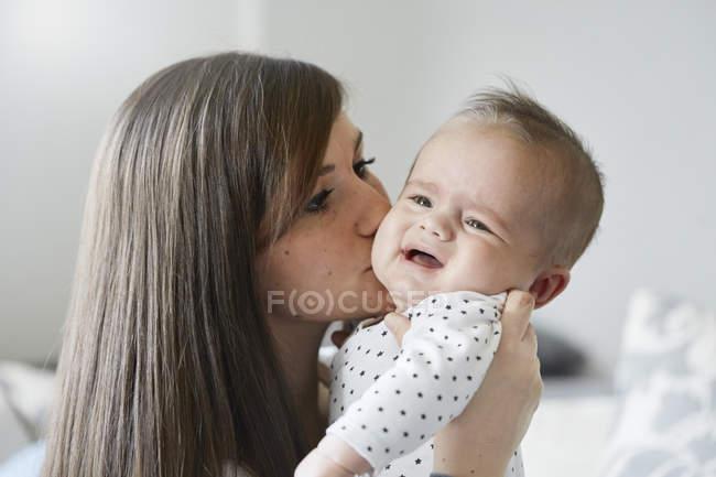Junge Mutter tröstet weinendes Baby — Stockfoto