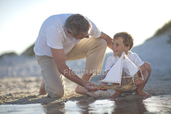 Father and son playing with a toy boat at a water pool on a sandy beach — Stock Photo
