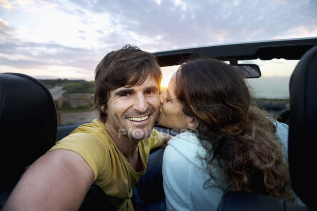 Happy couple in convertible at the coast at sunrise — Stock Photo