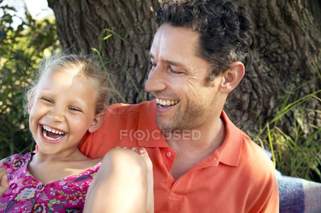 Padre feliz con hija en el árbol - foto de stock