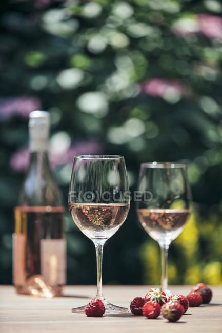 Dois copos de vinho rosé, garrafa de vinho, morangos e framboesas na mesa de madeira — Fotografia de Stock