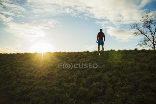 Молодой человек смотрит на восходящее солнце — стоковое фото