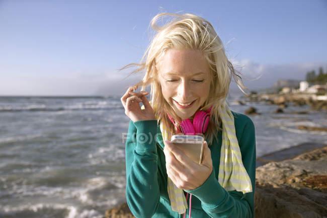 Souriante jeune femme avec téléphone cellulaire à la côte — Photo de stock