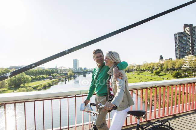 Germany, Mannheim, Mature couple crossing bridge, pushing bicycle — Stock Photo