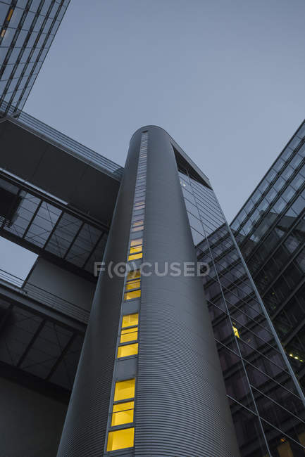 Germany, Munich, facades of office tower at evening twilight — Stock Photo