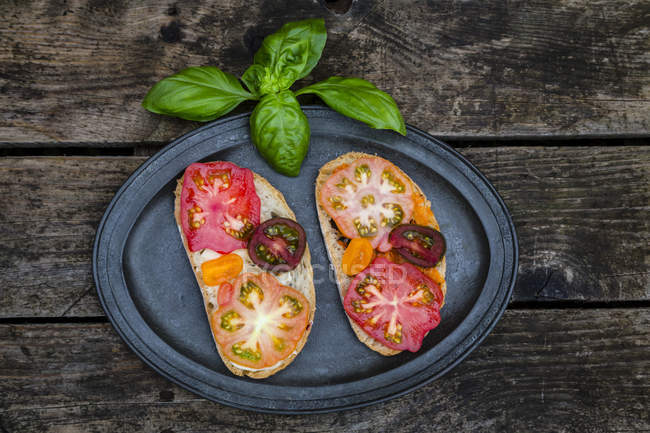 Tomato bread with Heirloom tomatoes and basil on a wooden table — Stock Photo