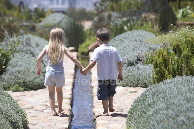 Menino e uma menina andando em um jardim com lavanda — Fotografia de Stock