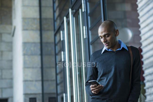 Uomo all'aperto guardando su smartphone — Foto stock