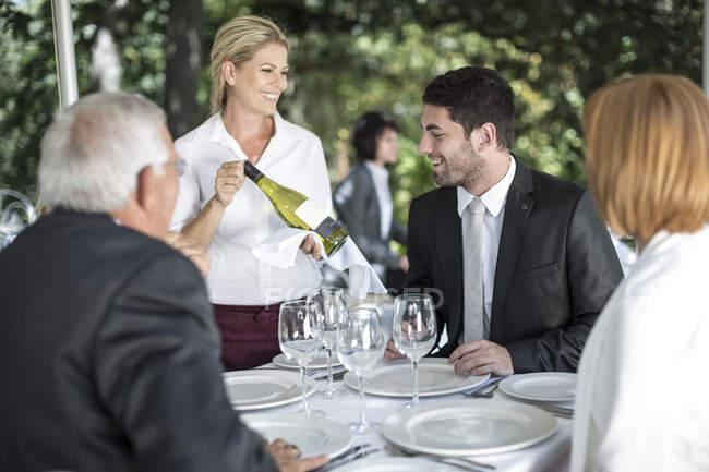 Cameriera Mostra vino bianco ai clienti al tavolo — Foto stock