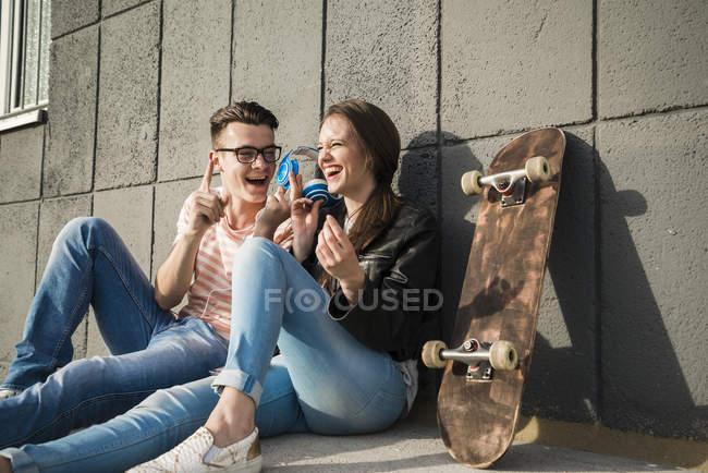 Feliz jovem casal sentado no chão com fones de ouvido e skate — Fotografia de Stock