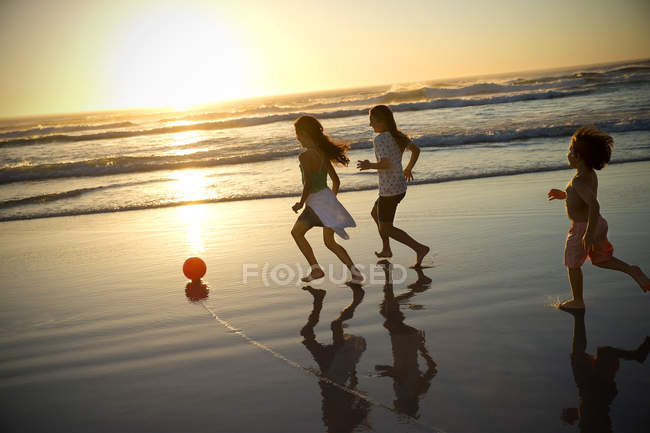 Three children playing with ball on the beach at sunset — Stock Photo